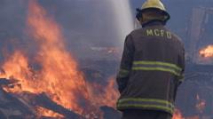 A firefighter sprays water on flames blazing above rubble from a house fire - stock footage