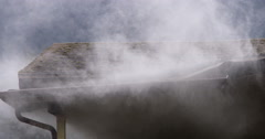 Smoke escaping from around gutter on the eaves of a burning house - stock footage