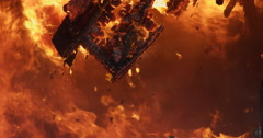 Burning, charred debris hanging in the middle of a raging fire - stock footage