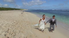 Bride and groom running on a sandy beach Stock Footage