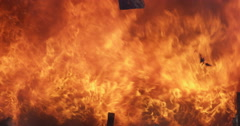 Falling debris in the middle of a raging fire, brief spray of water - stock footage