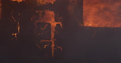 Debris falling into flames that devour the charred end wall of a burning house - stock footage