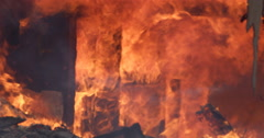 Rolling flames consume an interior wall of a burning house and debris falls from Stock Footage