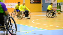 Player on the sidelines watching a game of wheelchair basketball Stock Footage