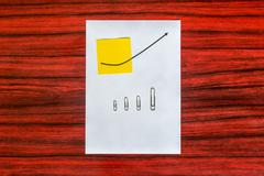 Curve graph printed on a sheet of paper and yellow note with arranged by size Stock Photos