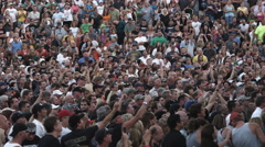 Crowd waving and cheering at the beginning of an outdoor performance - stock footage