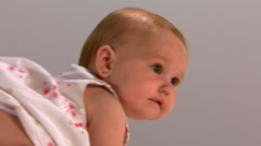 Baby in white sundress crawling and sitting up, close three-quarter profile shot Stock Footage