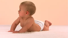 Baby in diaper lying on white rug, braced on hands and looking up - stock footage