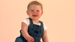 Seated baby in overalls waving at camera Stock Footage