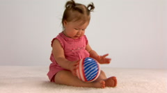 Seated baby girl playing with stars-and-stripes ball - stock footage