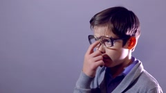 schoolboy tired rubs his forehead perspiring glasses Stock Footage