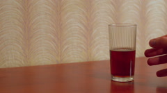 The man with a trembling hand takes the glass and drinks the alcohol - stock footage