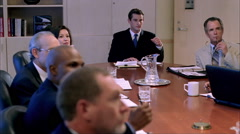 Executives seated around conference table, listening to speaker and taking notes Stock Footage