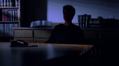 Businesswoman in a darkened room, looking thoughtful and serious Stock Footage