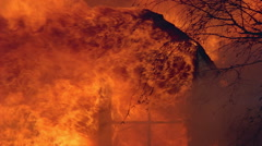 Flames of  house fire engulfing gable window - stock footage