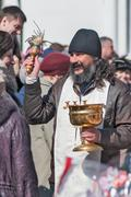 Priest blessing people with holy water. Tyumen - stock photo