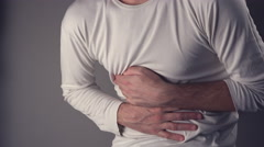 Man suffering from stomach ache, holding his belly and having painful cramps. Stock Footage