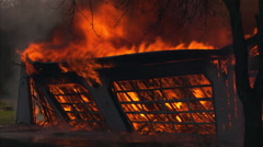 Wall of burning garage collapsing - stock footage