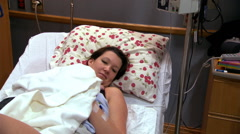 Young mother and newborn in hospital bed, nurse taking baby out of room Stock Footage