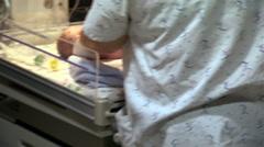 Nurse lifting newborn baby boy onto scales Stock Footage