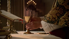 Priest elevating the chalice of wine during Eucharist Stock Footage