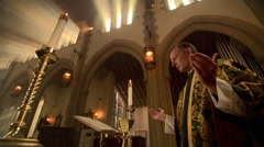 Priest at altar, lifting bread and wine during Eucharist Stock Footage