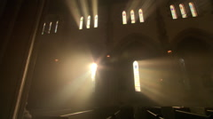 Priest walking down the aisle in darkened nave of Catholic church - stock footage