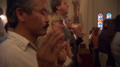Side view of standing congregation reciting the Lord's Prayer - stock footage
