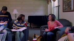 Co-ed college students gathered for group study time in a dorm's common area Stock Footage