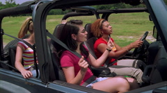Four happy college girls riding in an open jeep through a park-like area - stock footage