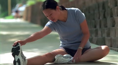 Young female jogger seated on sidewalk, doing stretching exercises Stock Footage