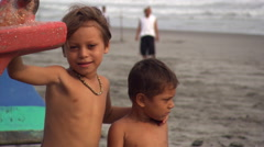Brothers getting their picture taken on Salvadoran beach - stock footage