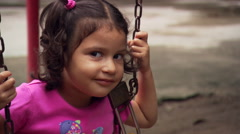 Close-up of little girl on a swing in Salvadoran park - stock footage