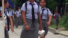 Children getting out of school pass camera on Salvadoran street Stock Footage