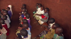 Children in African classroom, seen from above, clapping and singing to Stock Footage