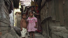 Children in Calcutta alley posing for portrait as mother looks on Stock Footage