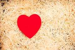 Love cradle with red heart and straw - stock photo