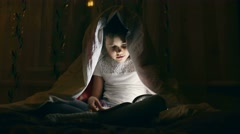Girl reading a book with a flashlight under the covers at night Stock Footage