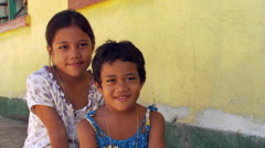 Smiling Samoan sisters sitting for portrait in front of yellow stucco wall Stock Footage