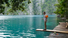 Girl jumping into the lake Stock Footage