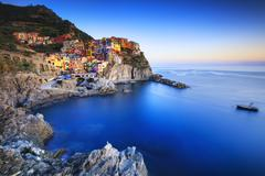 Stock Photo of Manarola village, rocks and sea at sunset. Cinque Terre, Italy