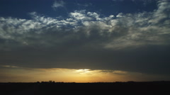 The sun sets beneath a layer of time-lapse clouds over a prairie landscape Stock Footage