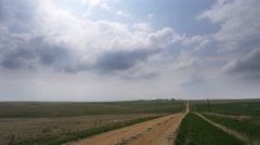 Time-lapse clouds and their shadows race over the prairie toward farm buildings Stock Footage
