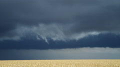 Bands of time-lapse storm clouds over a ripe wheat field Stock Footage