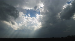 Sun rays through time-lapse white and stormy gray clouds sweep across the - stock footage
