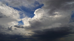 Dark gray time-lapse clouds pass in front of billowing cumulus Stock Footage