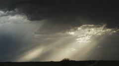 Time-lapse dark clouds pierced by sunbeams glide across the prairie at dusk Stock Footage