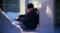 Elderly man sitting on snowy street corner and holding out cup to passers-by - stock footage