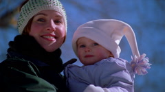 Close-up of mother and child in arms, both dressed in winter outdoor clothing - stock footage