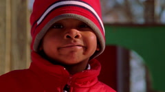 Close-up of smiling boy in red hat and coat Stock Footage